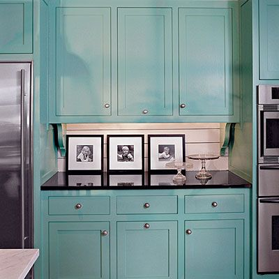 Peacock blue painted cabinets with black countertop laundry room