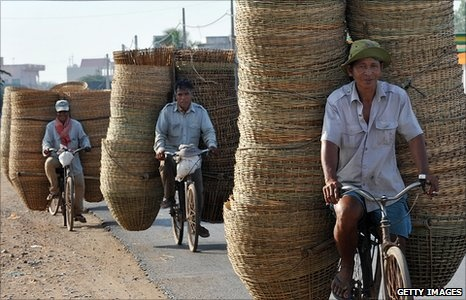 Cambodian vendors ride bikes loaded with baskets.