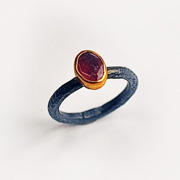 Katia Ruby Ring by Found Object. A single ruby nestled in a 14k gold-plated setting and oxidized silver band from Turkey. $90. So simple and unique!