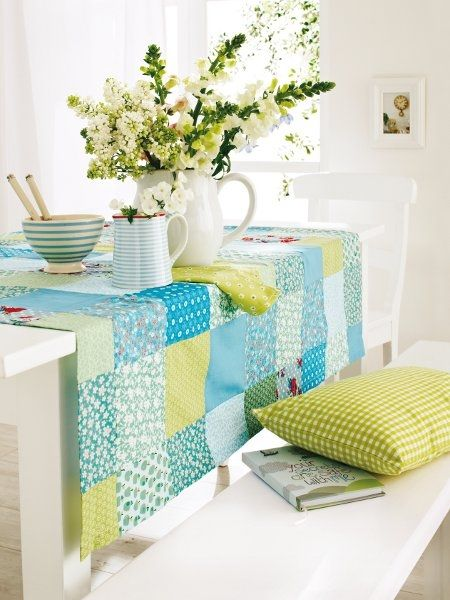 Patchwork table cloth in a bright colored kitchen.