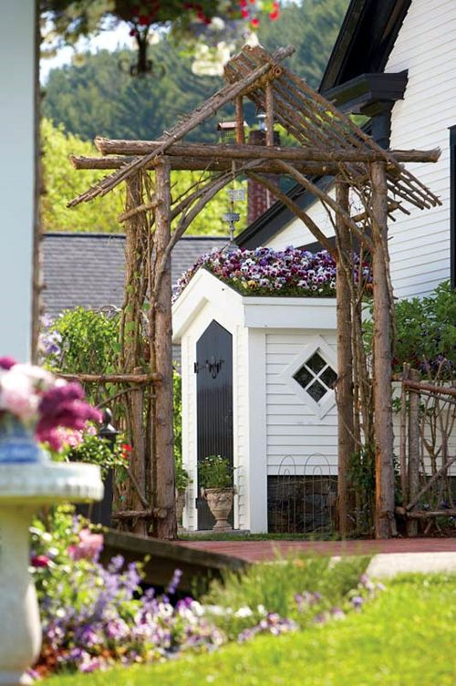 "I would name this a ""Carpenter Gothic"" arbor, due to the design and craftsmanship involved. It appears to be permanently installed. An arbor similar to this, made of driftwood, could be used for a wedding and afterwards, installed in the garden of the newlyweds.  That would be some present!"