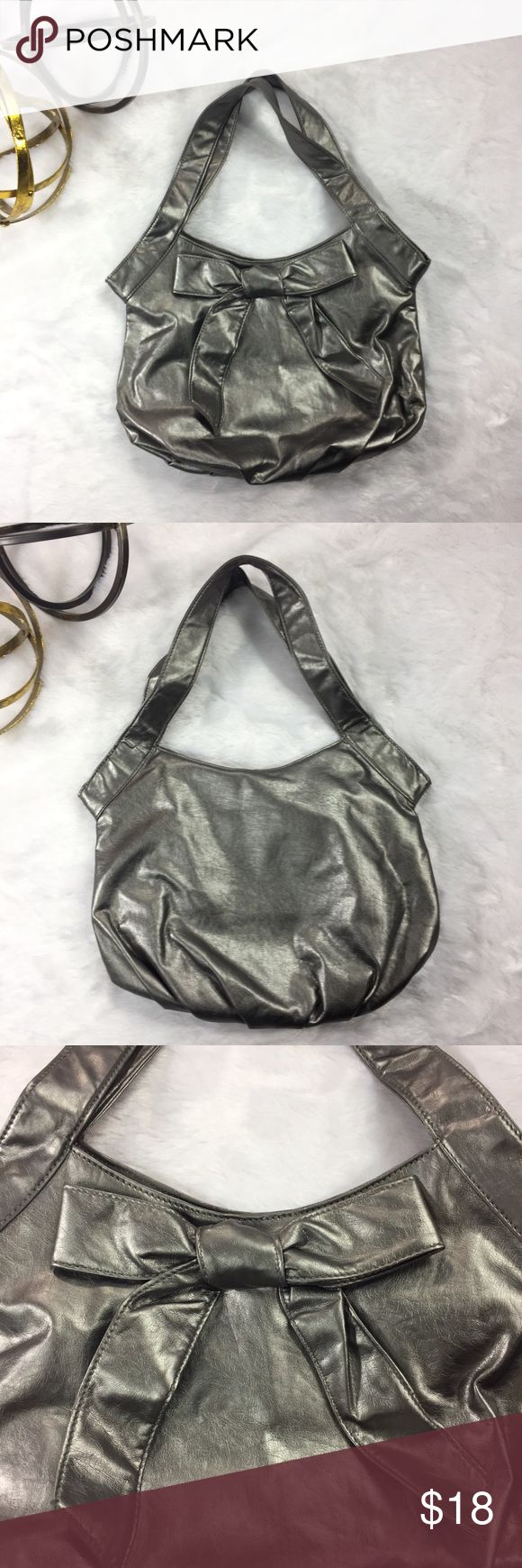 """Metallic Silver Shoulder Bag Metallic Silver Shoulder Bag. Bow in front. Metallic snap closure. Man-made material. No brand name available. Approximate measurements (measured flat): width: 14"""", length: 11.5"""", drop: 20"""". Excellent used condition. No signs of wear. Bags Shoulder Bags"""