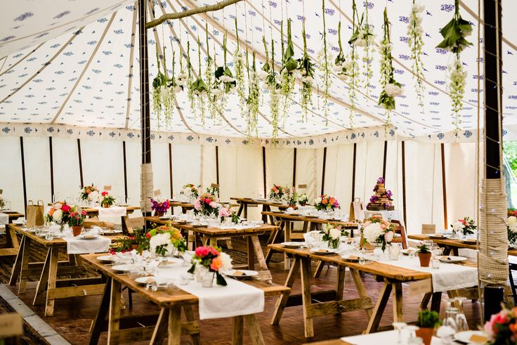 A 40' x 60' Traditional Canvas Pole Tent with Blue Block roof lining and cream walls and beautiful flowers!