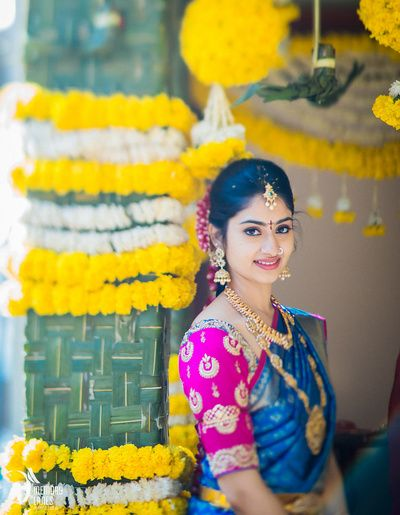 south indian bride, candid bride, bride portrait, blue and gold saree, silk saree, pink blouse, gold haar, red flowers in hair