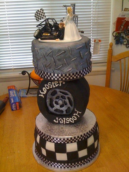 This is almost perfect...  Racing Themed wedding cake - this was for my sister who married a modified class racecar driver...wilton topper was used and then i added details to make it look like she is pulling him out of his shop/car garage.