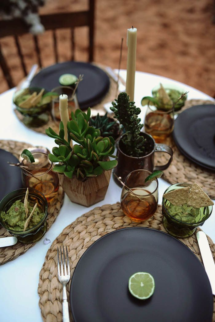 Southwest-inspired reception table decor with woven chargers, black plates, mini succulents, and bowls of guacamole | Image by Haley Nord Photography