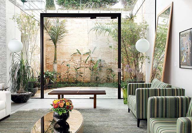 A esquadria é mínima para aproximar ainda mais a sala do jardim, que tem palmeiras-garrafa, helicônias e um imponente muro de tijolos de demolição. Os arranjos de zínia e de flor-de-alho foram feitos pela paisagista