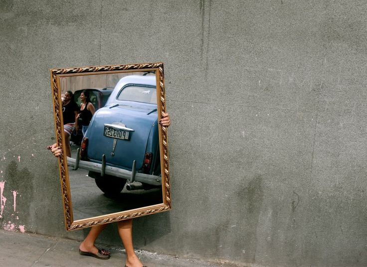 Woman moving mirror Photo by Mark Underwood — National Geographic Your Shot