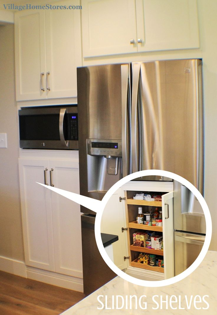 A built-in microwave is located in the center of a tall pantry cabinet that has ...