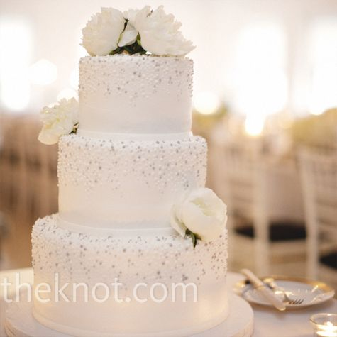 The three-tiered buttercream cake was dotted with gray and silver and topped with white peonies.