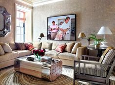 Modern living room ideas by Michael S Smith | A family room in beige color schemes with sectional sofas and a Jean de Merry low center table.