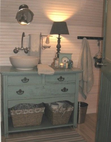 A pretty blue vintage chest is topped with a vessel sink to create a unique cottage-style vanity. Baskets underneath increase storag