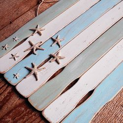 Turn ordinary paint stir sticks into a beach themed flag for your coastal decor!  DIY: wall art