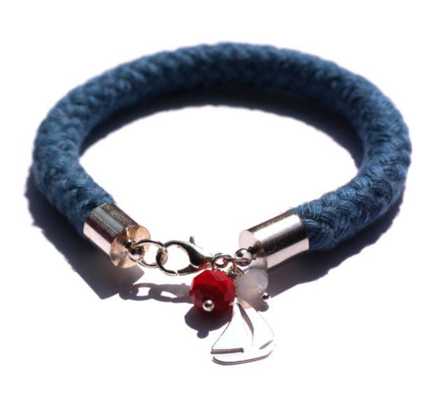 Handgefertigtes Armband in Dunkelblau mit SWAROVSKI ELEMENTS in Rot und Weiß und einem Segelboot aus 925 Silber. Die Verschlussteile sind versilbert. Länge des Armbands 20cm, Länge individualisierbar.