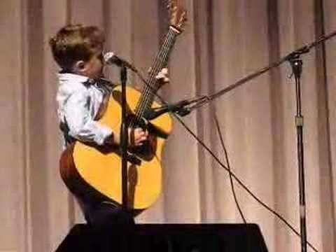 Here he is one year later. He performed again during a concert put on by city schools. This kid is in the 2nd grade, yes, 2nd grade. His guitar playing has really improved. He does an excellent job