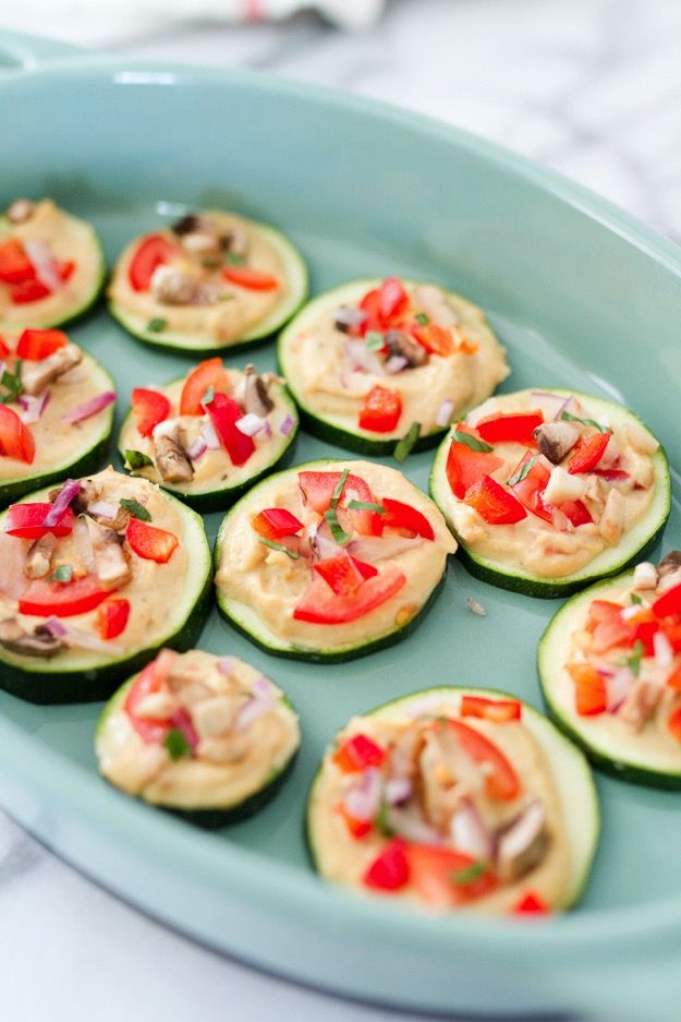 Mini Zucchini Hummus Pizza Bites // Satisfy your pizza craving with these healthy mini zucchini pizza bites. Raw zucchini serves as the crust while hummus and fresh veggie toppings give the bites that pizza flavor you crave.