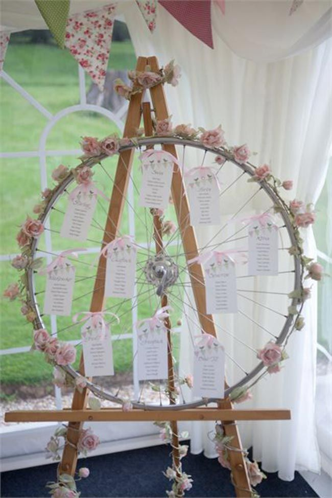 I love how something as simple as an old bike wheel can be made beautiful with roses and is actually a perfect way to display a table plan!