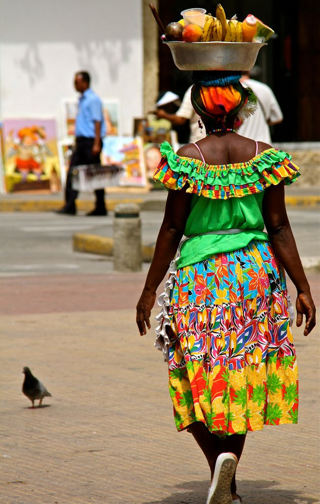 Las Palenqueras are the famous ladies dressed in vibrant colours carrying fruit baskets on their head. They are from the city of San Basilio De Palenque which is one hour away from Cartagena, Colombia.  They symbolize the struggles of the black cimarrones - slaves who courageously escaped from their owners in search of a better future.  by flower_bee