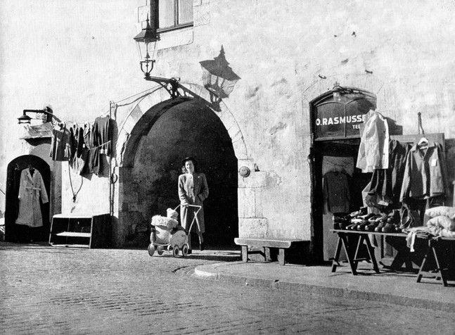 Oline Rasmussen solgte manufaktur, sjømanns- og fiskeriutstyr, arbeidsklær og støvler i sin butikk i Muren. Butikken ble startet i 1927. Fotoet er fra Arne Moe Nilssens bok «Fra min kjære by» som ble utgitt i 1947.