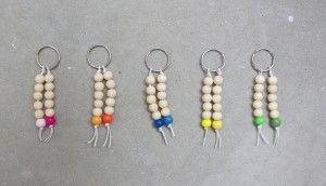 Leuke sleutelhanger met 2 koordjes met kralen. Ieder koortje bevat 5 blanke houten kralen en 1 kraal in een kleur (een neonkleur en een zachte kleur). Verkrijgbaar in roze, geel, oranje, groen en blauw.