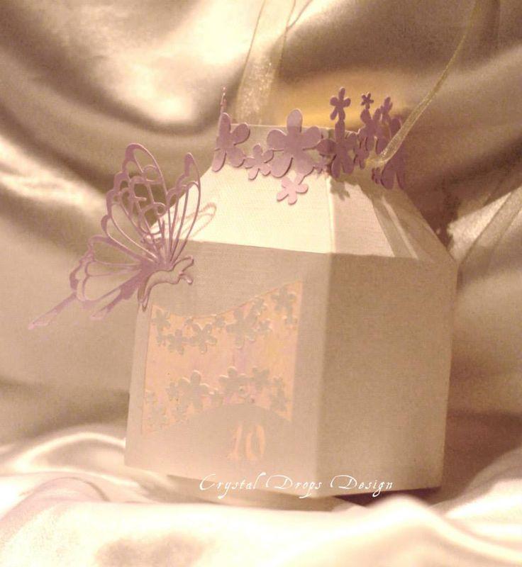 """Lanterna in carta gommata bianca alto grammaggio, con farfalla filigranata con monogrammi e fiori intagliati ed applicati su bordo in carta perlescente rosa. Con nastro in organza e fiori intagliati su due dei quattro lati. Trasparenze ottenute con carta seta rosa. Intaglio inferiore destro numero """"10"""" (modificabile con altro numero)   Dimensione 10 cm circa di lato."""