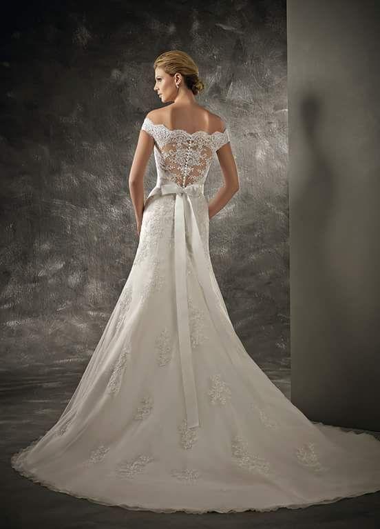 abito sposa, scollo a barca, ricamato; schiena con trasparenze e fiocco sul punto vita; ampia base del vestito