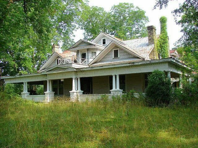 Abandoned house with large, covered front porch.