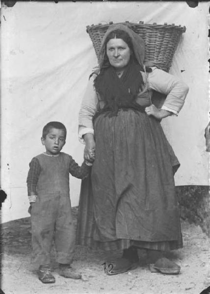 Val Brembana. Ritratto di contadina con gerla sulle spalle e bambino per mano