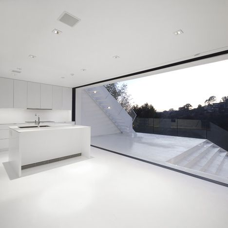 The rooms of a black and white house in California lead out to a series of stepped terraces with a view of the famous Hollywood sign.