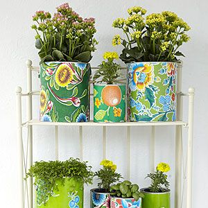 Decorate your patio with this easy summer craft: Dress up empty paint cans in bright, cloral oilcloth to make your own decorative planters.
