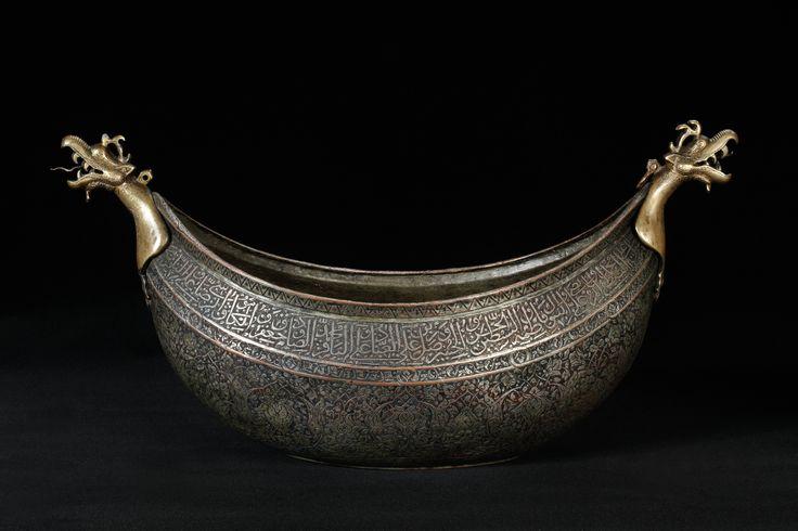 Tiggerskål (kashkul) af graveret og fortinnet kobber (nok ophamret). Endestykker af støbt messing Iran; 16. århundredes 1. halvdel