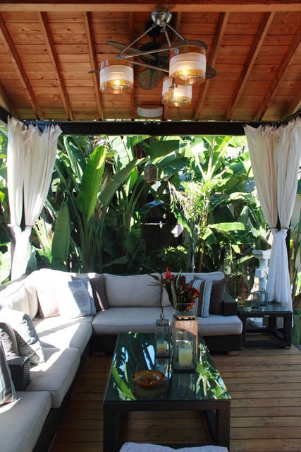 Garden screening to create an oasis. Also love the outdoor lounge and luxurious resort feel created through the lamps, fan and curtains.