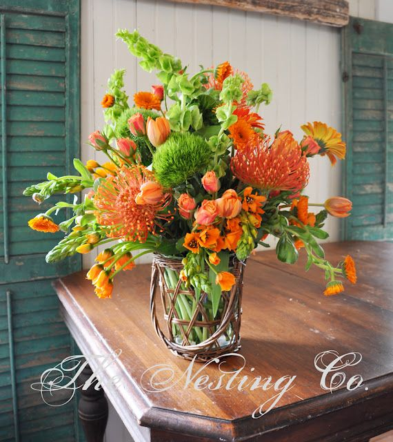 Bells of Ireland, green trick, orange spray roses, orange tulips, orange calendulas and pincushion protea flower, made by Heidi Jaster of The Nesting Co. Florist.