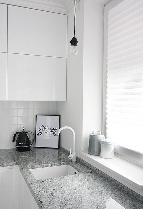 Minimalistic white kitchen. Granite counter. Scandinavian style.