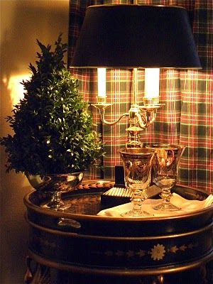 Christmas vignette: tartan curtain, black & gold table with a silver urn that holds a boxwood tree - Beaux Mondes Designs
