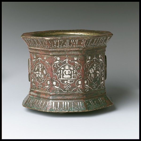 Mortar made for Abu Bakr 'Ali Malikzad al-Tabrizi. Date: late 12th–early 13th century. Geography: Iran. Culture: Islamic. Medium: Brass; cast, chased, engraved, and inlaid with silver and black compound. Dimensions: Mortar: 91.1.527a H. 4 1/2 in. (11.4 cm) Diam. 5 3/4 in. (14.6 cm) Pestle: 91.1.527b H. 10 1/2 in. (26.7 cm) Diam. 2 3/8 in. (6 cm). Accession Number: 91.1.527a, b.