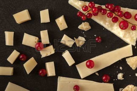 Overhead shot of pieces of cheese and redcurrant scattered on black table. Stock Photo