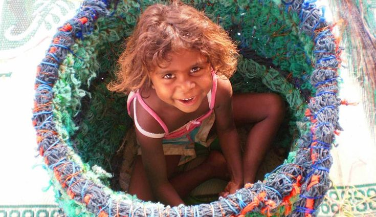 The Ghost Net Art Project: Shekeena Pahimbung easily fits into this basket as it was being made during the first ghost net workshop in Aurukun in 2009. Photo by Sue Ryan.