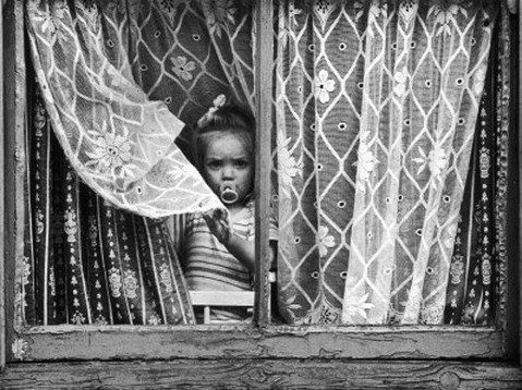 Little girl peers through net curtains, Salford, Greater Manchester, England, United Kingdom, 1964, photograph by Shirley Baker.