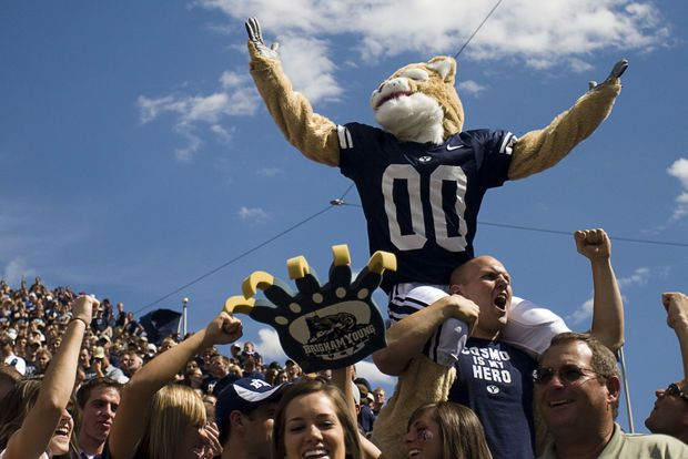 A fan lifts the BYU mascot, Cosmo, onto his shoulders as he cheers for the Cougars
