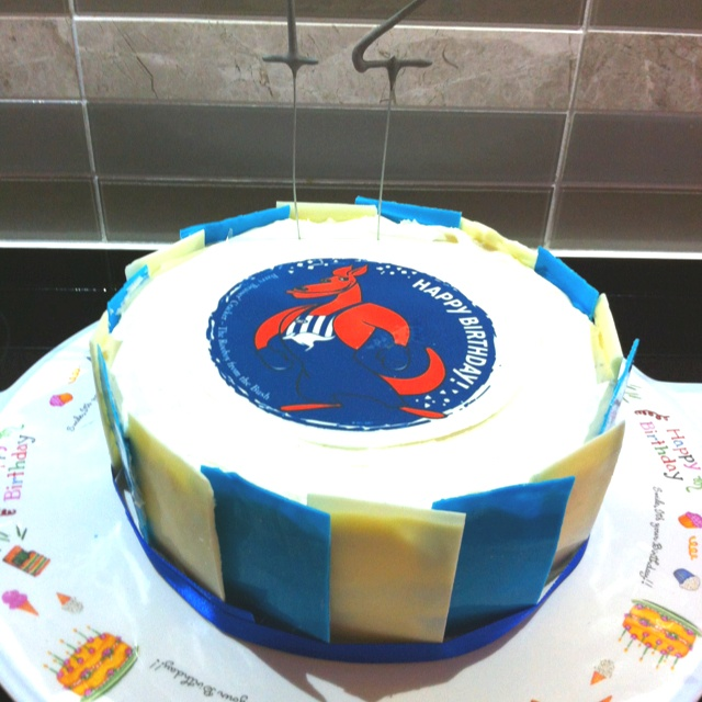 North Melbourne FC Cake. Edible cake topper and white and clue chocolate panels around the outside.