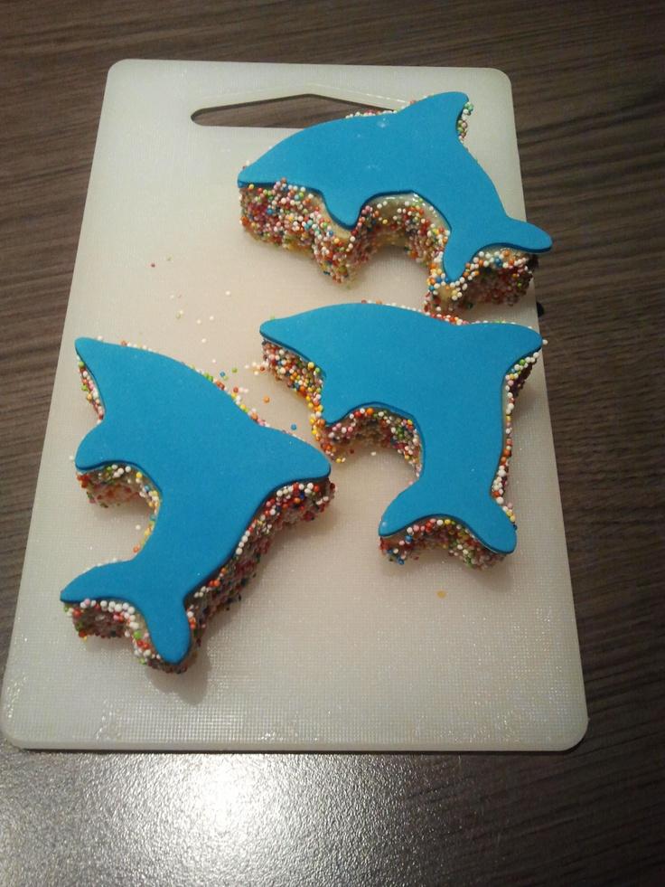 dolfijnen cakejes, snij met een koekvormpje een dolfijntje uit een plak cake, besmeer de zijkant met slagroom en dip de zijkanten in de spikkels, besmeer de bovenkant met slagroom, rol fondant uit en snij met de koekvorm een dolfijntje uit het fondant en plak dit bovenop het cakeje.