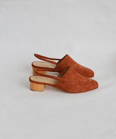 "An almond toe mule in warm rust suede with a slight wooden heel. SPECS: -almond toe mule -sling back strap -rust suede -100% suede -1.75"" wooden heel -made in Portugal ABOUT THE DESIGNER: French ceram"