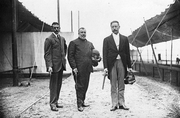 Sir cosmo Duff Gordon (right) poses with W.Bean and captain MacDonnel, holding duelling pistols and protective masks, 1912