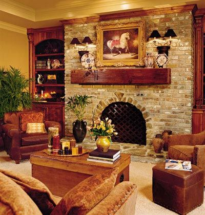 The Warmth of Brick    Warm wood, lots of brick, and rich furnishings envelope this family room's fireplace.    In this welcoming and cozy den, New Orleans red brick covers the wall from the hearth to the crown molding. An oval arch surrounded by natural stones forms the firebox opening, while a cross-hatch firescreen adds visual play to the brick wall.