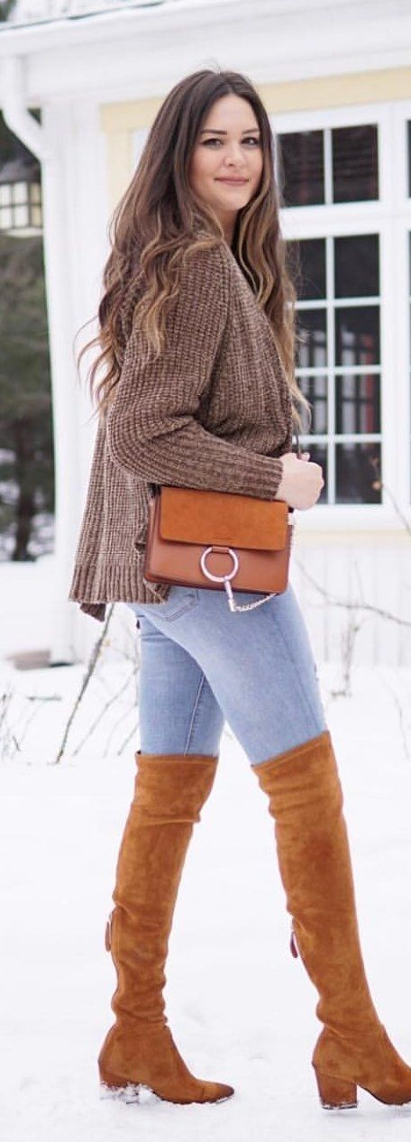 #spring #outfits woman wearing brown sweater and brown suede knee-high boots walking on snow near a white house. Pic by @mash.elle