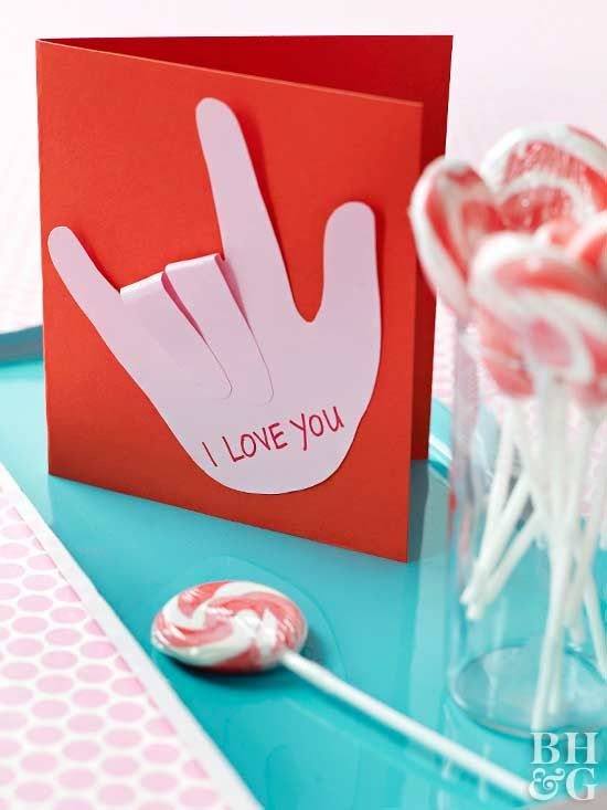 """This card is cute, clever, and simple: perfect for creating multiple valentines! Kids will love tracing their own hands and cutting out the shapes on different colors of paper. Glue the palm of the paper hand to the card, then glue down the thumb, pinkie, and pointer finger. Fold over the remaining fingers and secure with glue to form the American Sign Language """"I love you"""" gesture on your card."""