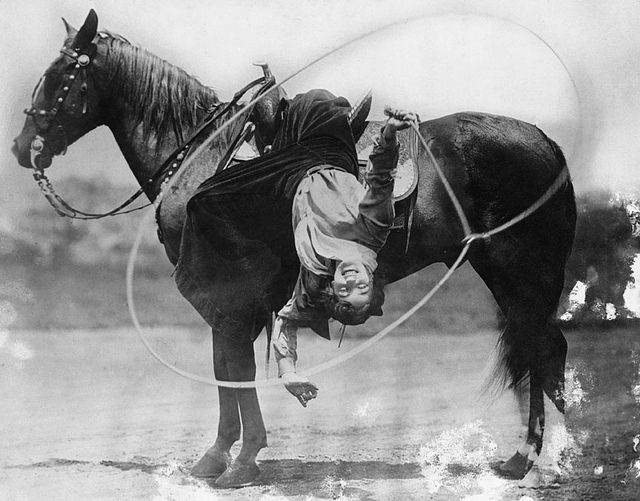 """Flores La Due performing fancy rope trick at the Calgary Exhibition and Stampede, c.1912.  """"A girl who knows the ropes is not likely to get tied up."""""""