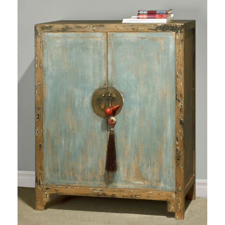 Ming (1368-1644) furniture style is characterized by its simple, clean and pleasing lines. Our rustic reproduction Elmwood Ming cabinet is a fine example of the sleek design, emphasized by the trademark hand-forged round hardware. Two removable shelves behind the doors give you ample storage for your CDs or books. Handcrafted by master artisans in China. Distressed blue finish. Doors are paired with Chinese lucky pendant and gourd silk tassel.  Fully assembled.(White glove service available…