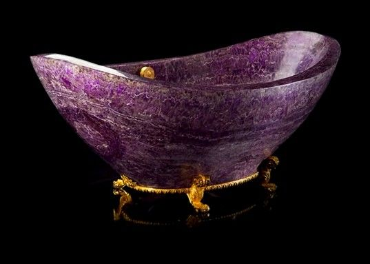 a stand-alone tub made of amethyst, one of the most precious stones and is based on a stand with golden accents to add to the grandeur.